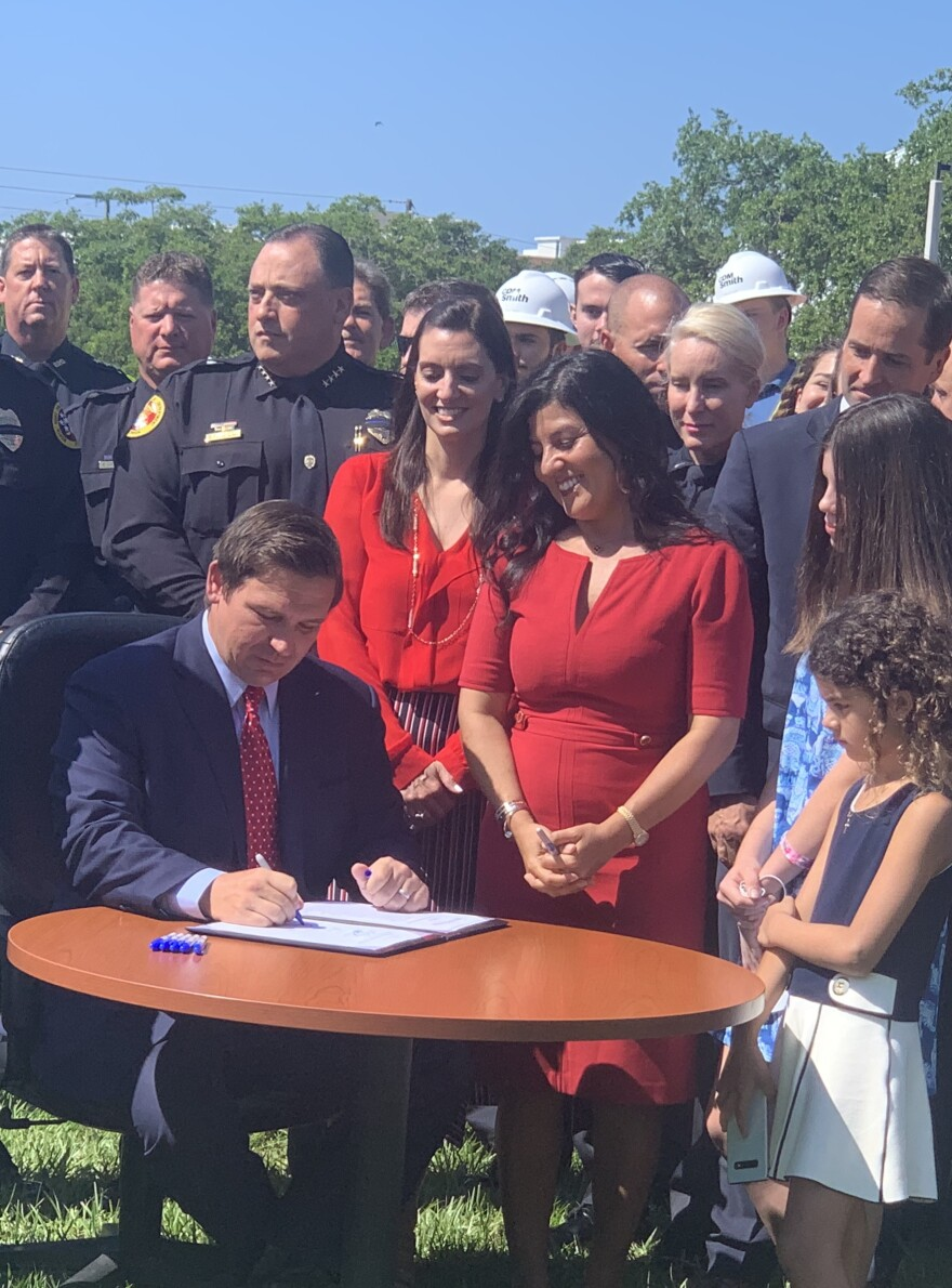 Governor sits at table signing bill