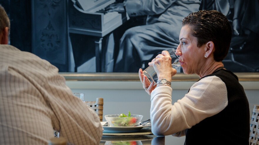 Deep brain stimulation eased Shari Finsilver's tremors, but didn't stop them entirely. Here she uses both hands to stabilize a glass of water.