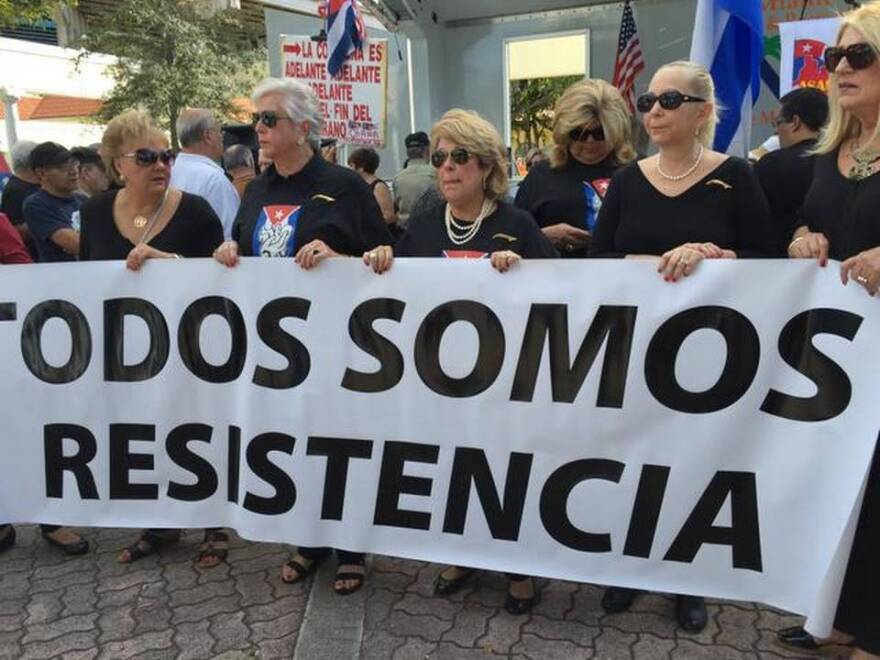 "Cuban exile protesters at a rally in Little Havana hold up a sign that says in Spanish: ""We are all part of the resistance."""