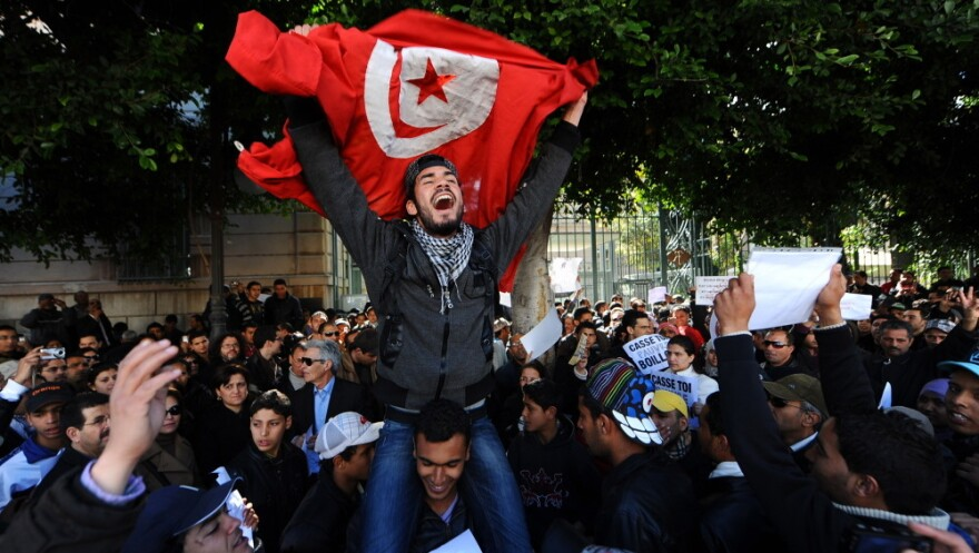 Tunisians protest outside the gates to the French Embassy in Tunis. Arab Spring began in Tunisia when a fruit vendor set himself on fire in protest in front of a government building.