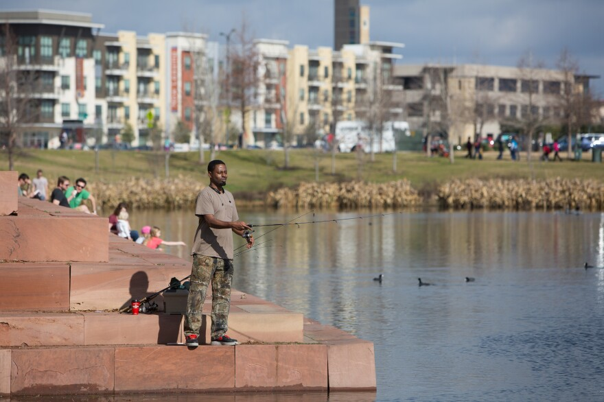 Ervin King fishes for bass and perch in Mueller's Lake Park. Developers decided to keep private yards small in favor of large public parks and green space, creating a destination outdoor space for the surrounding east Austin community.