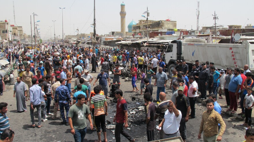 People gather at the site of a car bomb attack at a marketplace in the Sadr area of Baghdad on Wednesday.
