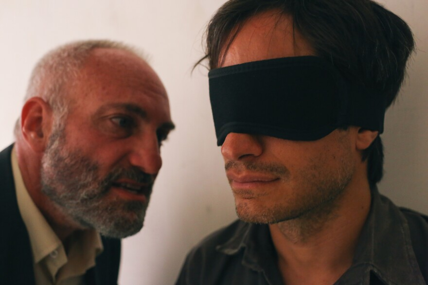 An Iranian security agent (Kim Bodnia, left) was Bahari's torturer in the film. He used a <em>Daily Show</em> clip as evidence that Bahari was a spy.