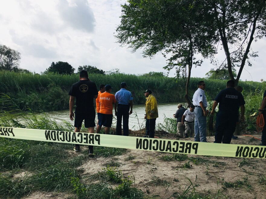 Authorities stand behind yellow warning tape along the Rio Grande bank where the bodies of Salvadoran migrant Óscar Alberto Martínez Ramírez and his 23-month-old daughter, Valeria, were found, in Matamoros, Mexico on Monday, after they drowned trying to cross the river to Brownsville, Texas.