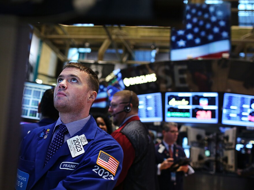 Looking up: Traders on the floor of the New York Stock Exchange earlier today.