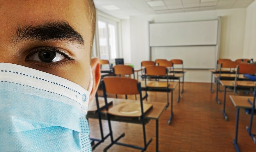 Person with mask, classroom in background