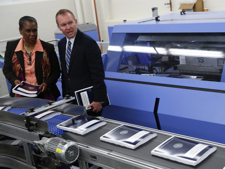 The Government Publishing Office's then-Director Davita Vance-Cooks (left) inspects the production run of President Trump's 2018 fiscal year federal budget with Office of Management and Budget Director Mick Mulvaney in 2017 at the GPO's plant in Washington, D.C.