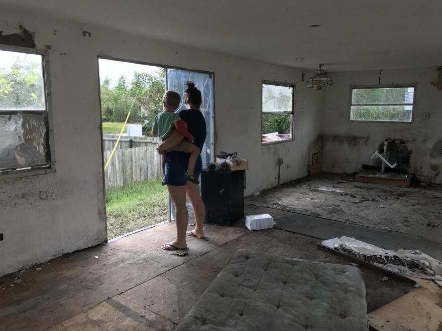 Patty Demere and her son Augustus looking out of where a sliding glass door used to be from the living room area.