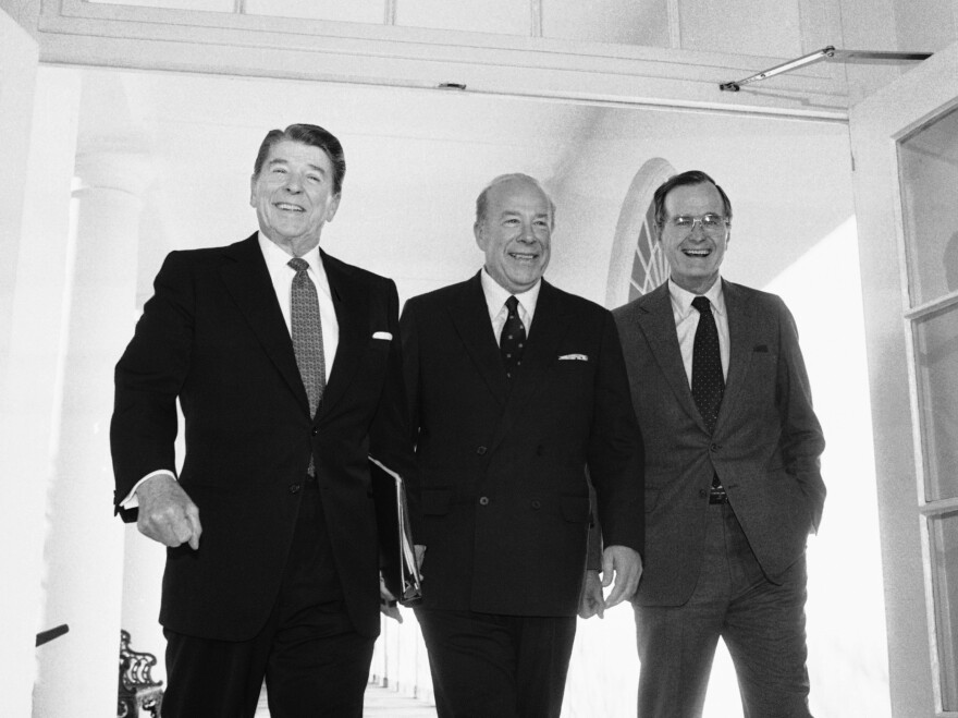 Secretary of State George Shultz, center, walks with President Reagan and Vice President George Bush on his arrival at the White House in January 1985 after two days of arms talks with the Soviet Union in Geneva. Shultz died Saturday at the age of 100.