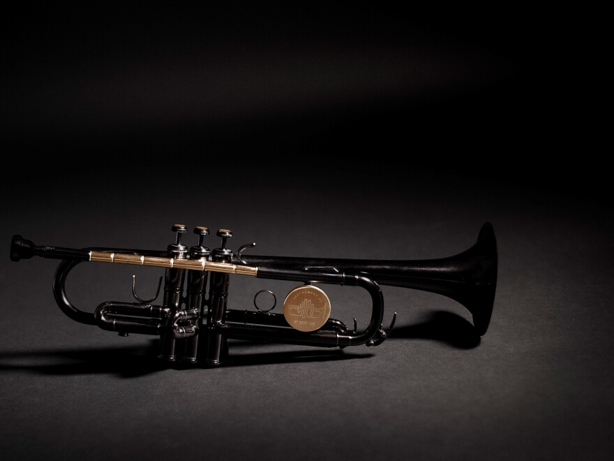 The Instrument of Hope is lacquered in black except for the shiny brass parts, which are clear lacquered. They include the lead pipe, which is made from bullets set end to end and drilled out so that air can flow through to make it a playable instrument. The tops of the three buttons are made of the sawn-off casing end caps or rims.