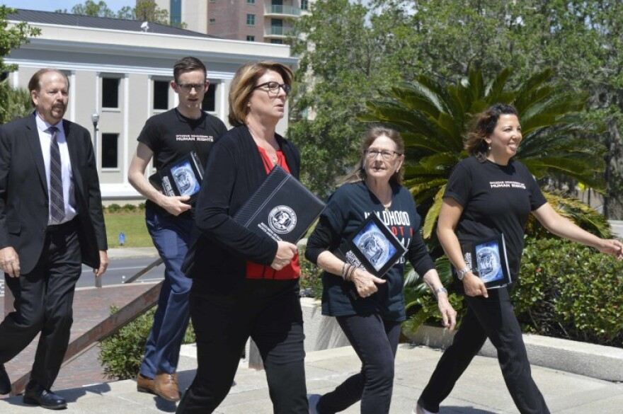 Members of the Citizens Commission on Human Rights, some in suits, walk on the grounds of the Florida Capitol with the Florida Supreme Court in the background.