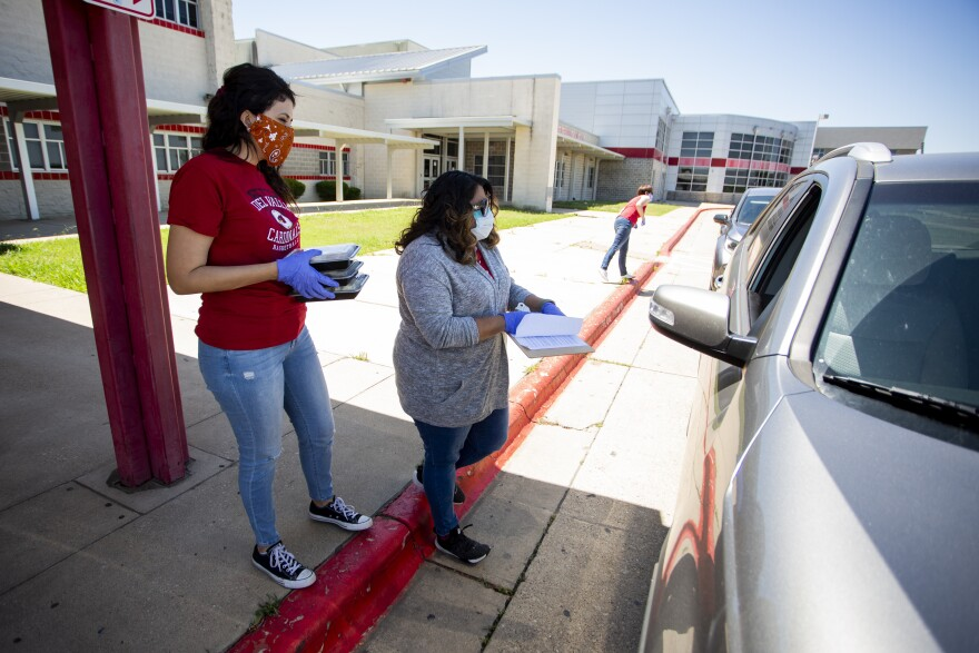 Del Valle Community Coalition members Vanessa Fuentes, Susanna Woody and Tina Byram (left to right) distribute food at Del Valle High School on April 30. The coalition is aiding residents during the coronavirus pandemic.