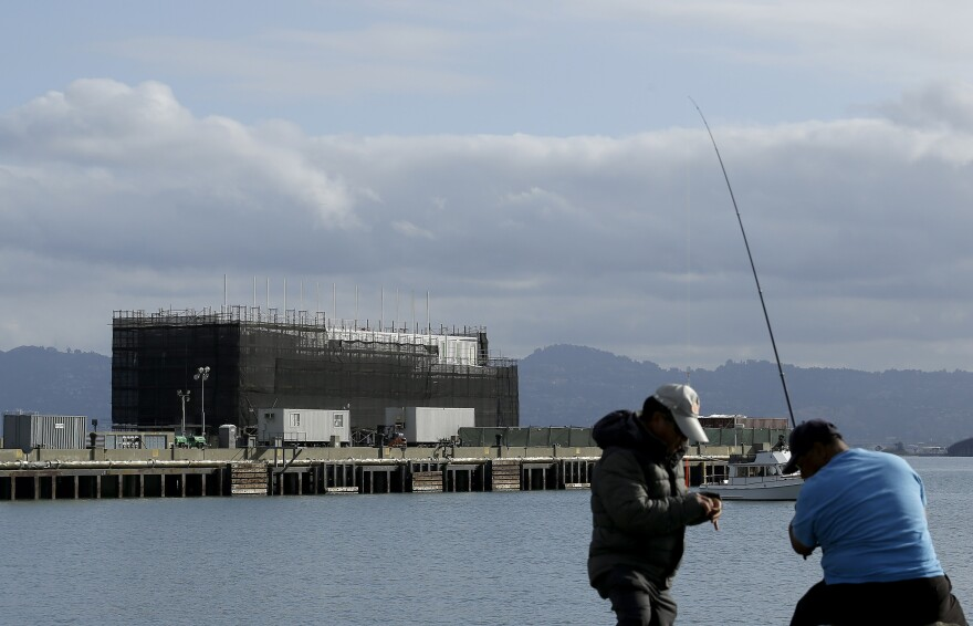 "Two men fish in the water in front of a barge on Treasure Island in San Francisco on Tuesday. An unnamed source tells CBS the barge carries a building ""constructed of interchangeable 40-foot shipping containers that can be assembled and disassembled at will, allowing it to be placed on barges, trucks or rail cars and taken anywhere in the world."""