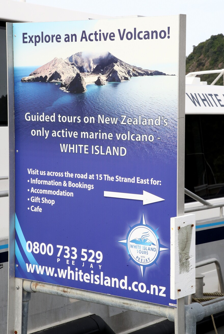 A sign at the Whakatane wharf advertises guided tours of the White Island volcano. Officials had recently released alerts warning that it was more active than usual.