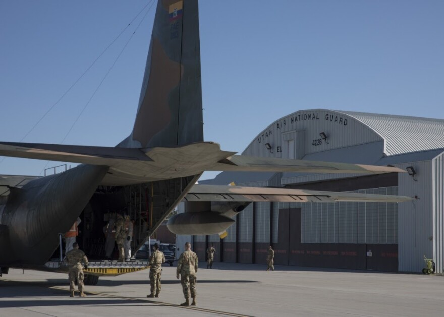 "Soldiers load a cargo plane. An aircraft hanger marked with the words ""Utah Air National Guard"" is in the background."