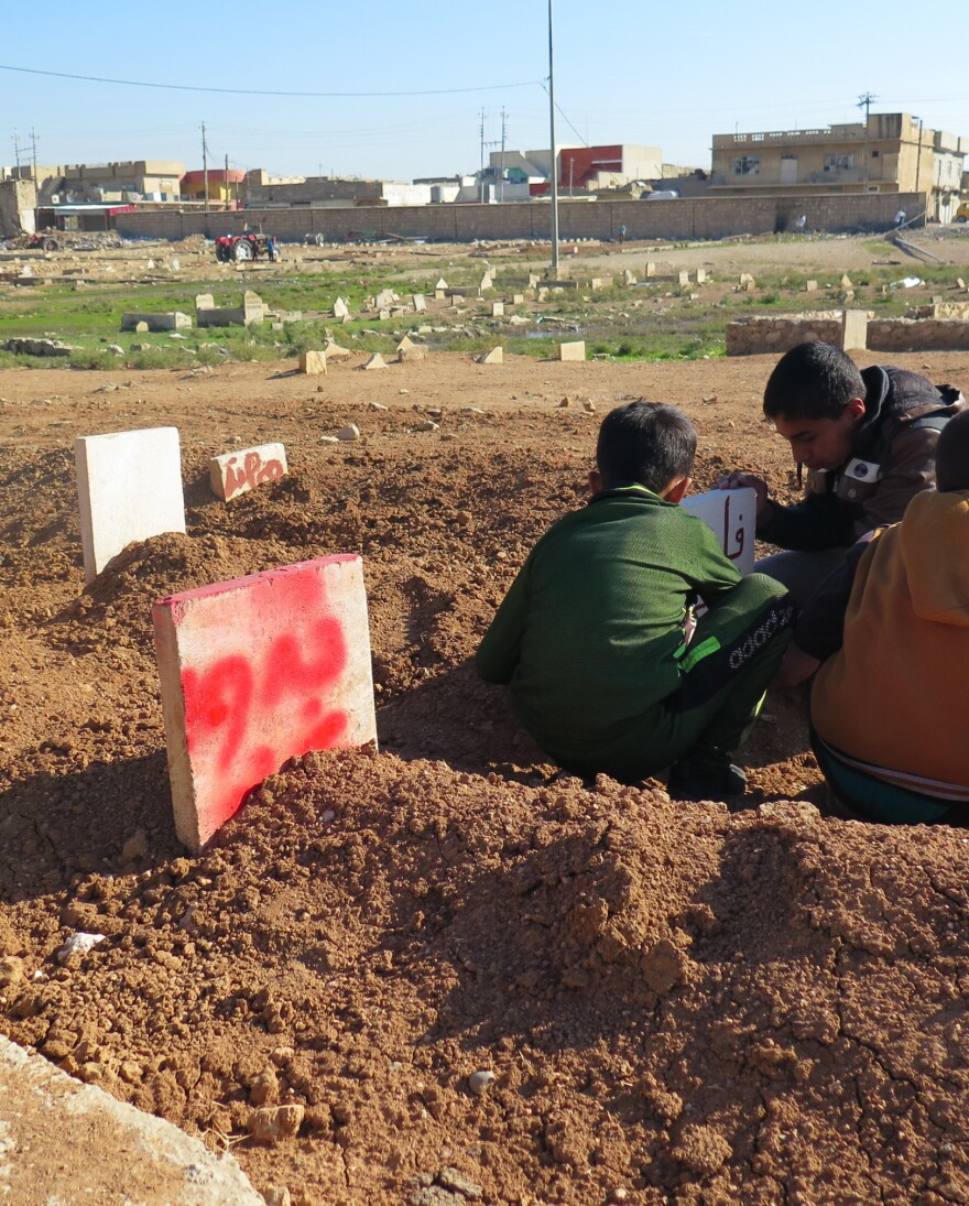 Neighborhood children reading gravestones. One is for Badawiya and Abed – a 15-year-old girl and her 6-year-old brother killed when their house collapsed during an airstrike in Mosul. She died with her arms around her little brother trying to protect him. Gravediggers said they couldn't pry them apart and buried them in the same grave.