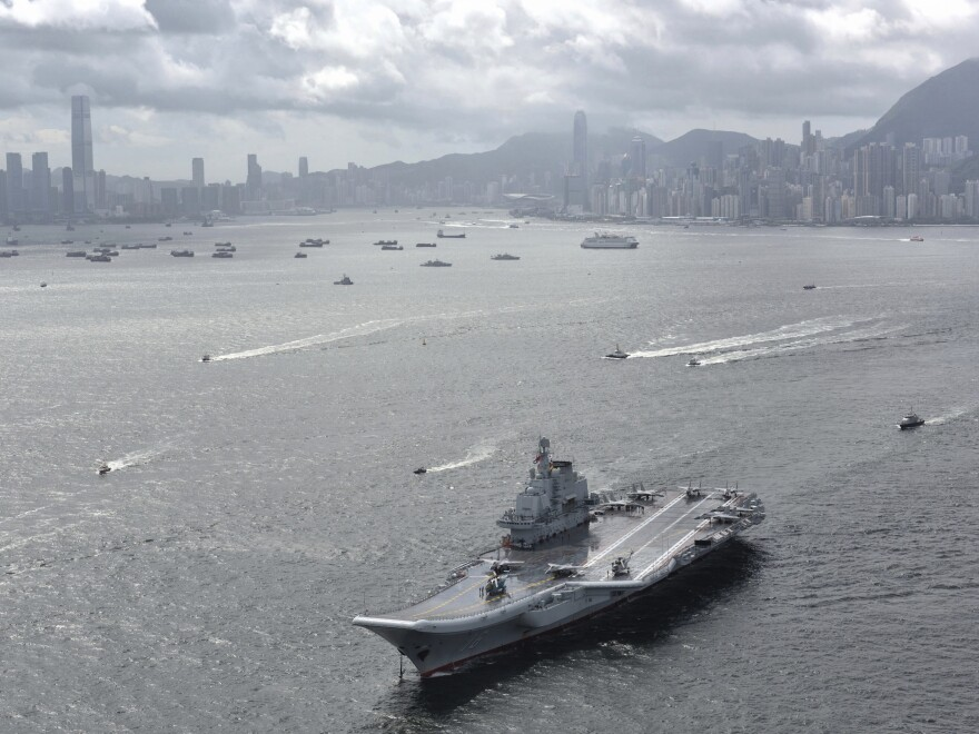 The Liaoning, China's sole operating aircraft carrier, steams into Hong Kong for its first port call in the city on Friday.