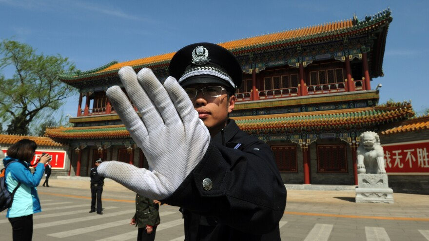 A police officer blocks photos from being taken outside Zhongnanhai, the central headquarters for the Communist Party of China, in Beijing last year.