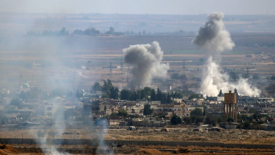 A photo taken from Turkey's Sanliurfa province shows smoke rising after Turkish armed forces hit targets in Ras al-Ain, a town east of the Euphrates River in northern Syria, on Monday.