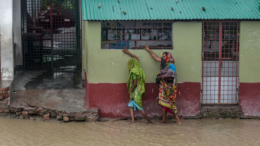 Residents gingerly tread a flooded street on their way to a shelter Wednesday in the border city of Khulna, Bangladesh.
