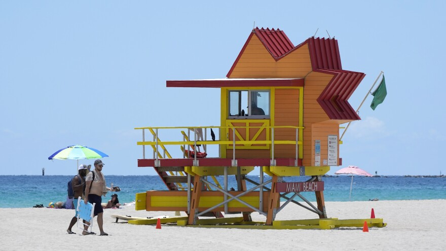 Beachgoers walk past a lifeguard tower on a nearly empty beach on Aug. 11 in Miami Beach, Fla.