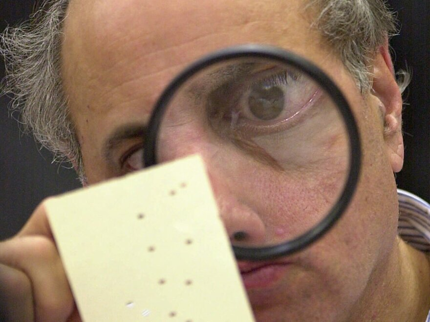 Broward County, Fla., canvassing board member Judge Robert Rosenberg uses a magnifying glass to examine a disputed ballot on Nov. 24, 2000.