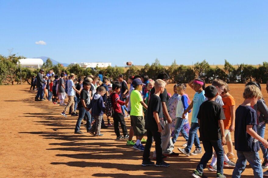 Photo of a line of young boys standing across from a line of young girls in the center of a red dirt corral.