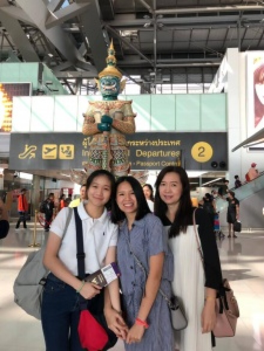 Annie Ramita, center, poses for a photo with her mother and sister in a Thailand airport