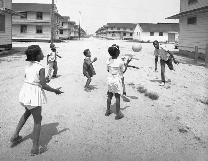 Some children of reverse freedom riders families toss ball among themselves amid Army barracks at Camp Edwards, Mass., June 11, 1962.