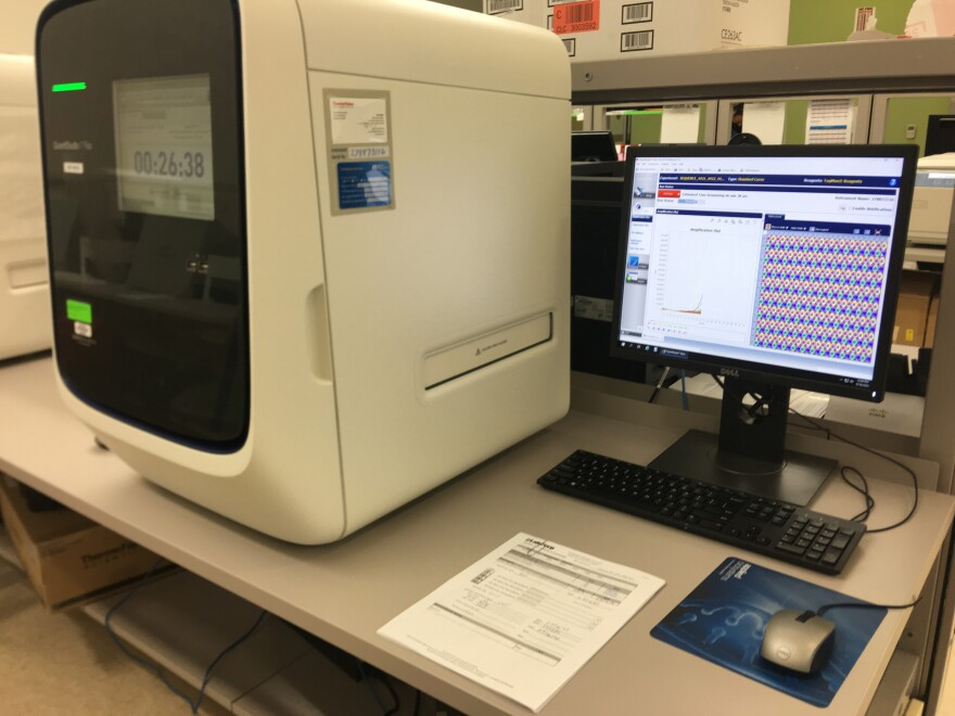 A machine works to detect genetic material from the coronavirus in patient specimens. Each colored line on the screen represents an individual patient.