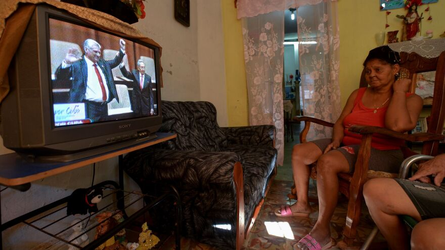 A woman watches outgoing Cuban President Raúl Castro (right) hoist the arm of his successor, Díaz-Canel, during a televised ceremony formally marking the latter's election.