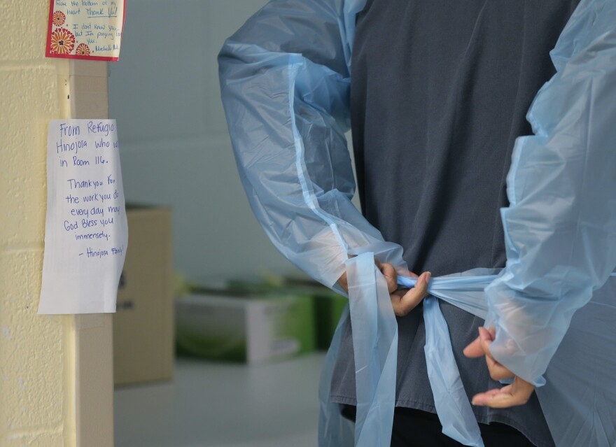 A medical worker ties the back of their protective gown.