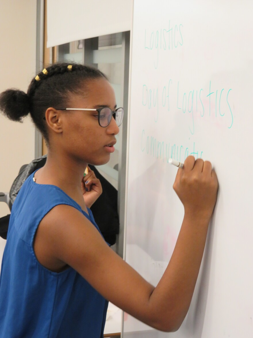 Student organizer Vikiana Petit-Homme, 16, writes out the agenda in advance of a meeting about joining a national student walk-out on March 14. That date marks one month since the mass shooting at a Florida school that left 17 people killed.