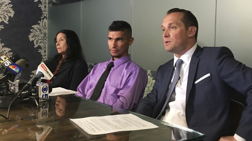 Jose Luis Conde (center) listens to news media while seated between his mother, Rosa Conde, and his attorney Bret Royle at Royle's office in Phoenix on Thursday. Royle released Mesa police body cam videos showing officers punching Conde, who was unarmed, and later mocking him while he was lying on a hospital room floor after his Jan. 28 arrest.