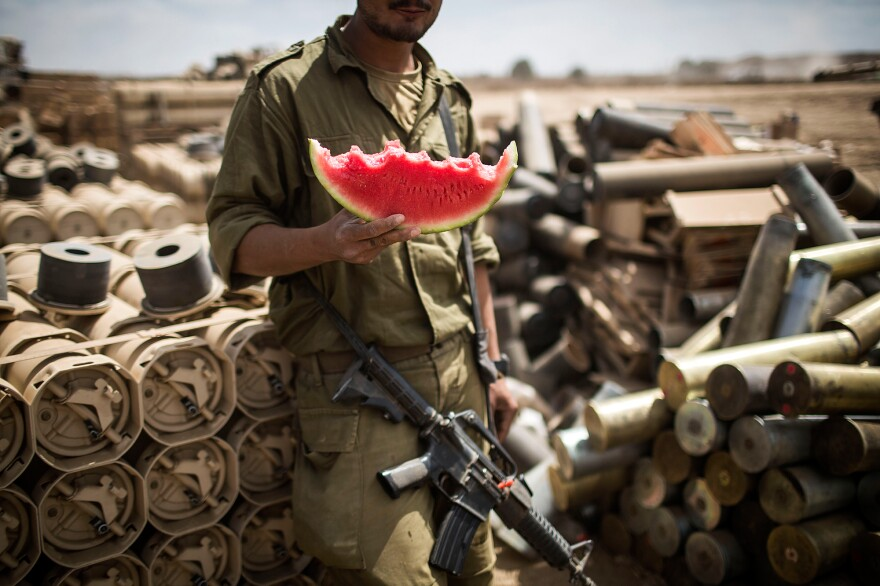 An Israeli soldier eats a piece of watermelon near Israel's border with the Gaza Strip in 2014. As more Israelis go vegan, the country's military has made dietary and clothing accommodations for soldiers.