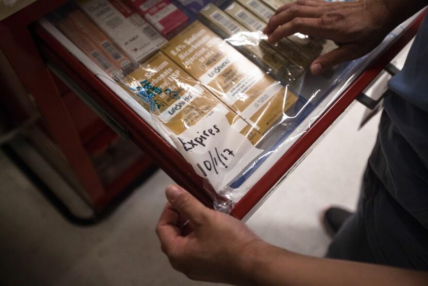 Pharmacy technician Nikki Wong sorts medications in drug boxes at Newton-Wellesley Hospital.