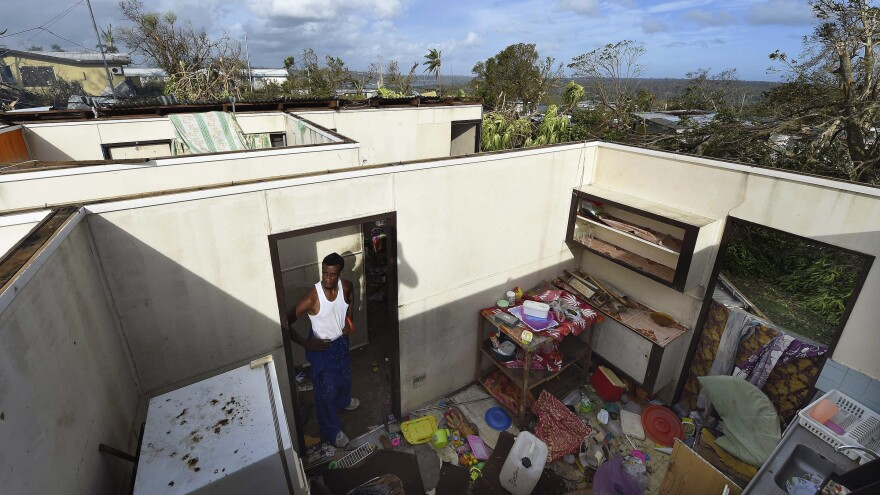 Resident Uwen Garae stands in his home damaged by Cyclone Pam in Port Vila, the capital city of the Pacific island nation of Vanuatu, Monday. The storm destroyed homes, smashed boats and washed away roads and bridges as it struck late on Friday and into Saturday.