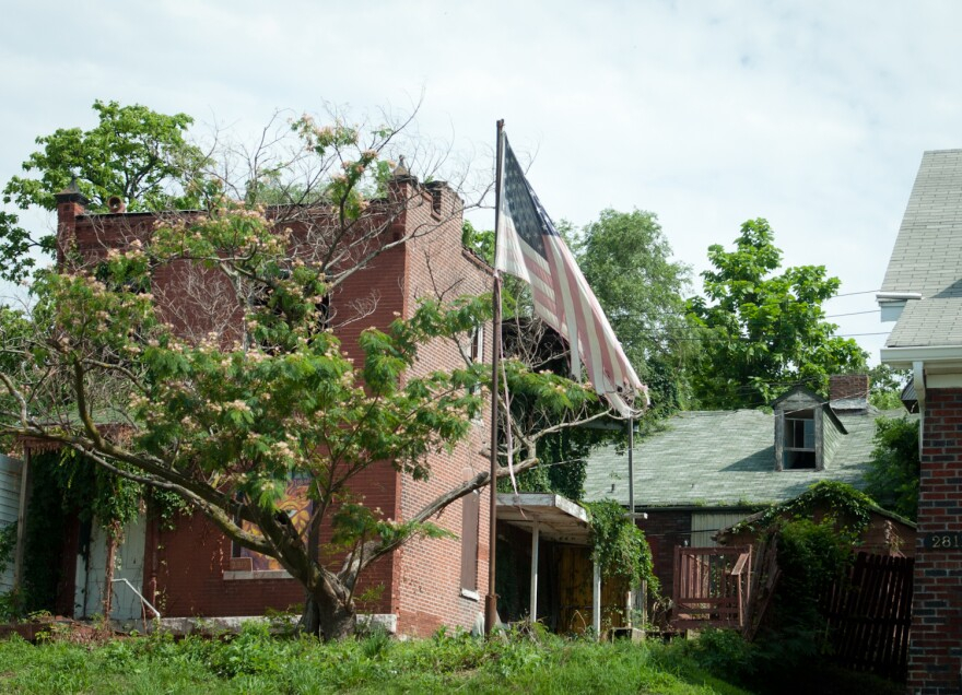 A faded and tattered U.S. flag catches the breeze in the yard of a vacant property in the Gravois Park neighborhood on June 30, 2018.