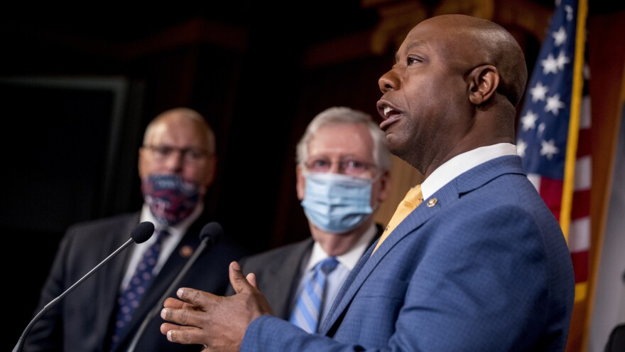 Sen. Tim Scott, R-S.C.,  right, addresses a news conference Wednesday to announce a Republican police reform bill on Capitol Hill.