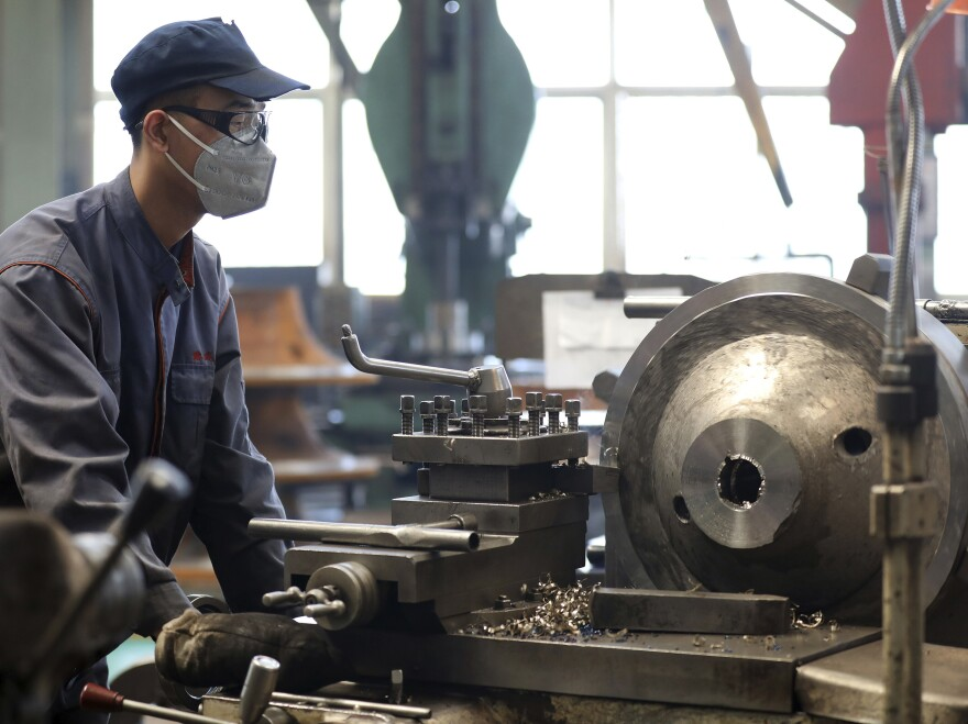 An employee wears a face mask as he works at a blower and fan manufacturing plant in northeastern China's Liaoning province. The economy contracted by 6.8% in the first three months of 2020 from the same period a year ago.