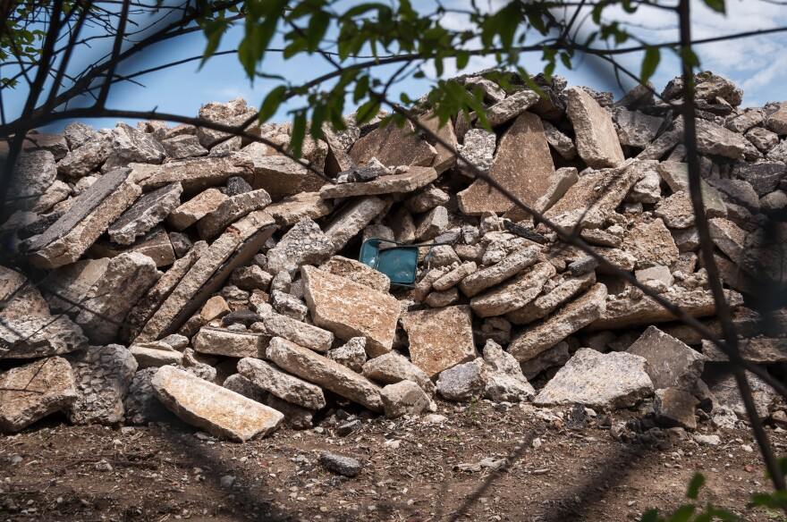 Piles of concrete and brick line a fence separating the former Pruitt-Igoe housing development from the Gateway school complex. Parents and staff at the school say placing the rubble there stirred levels of dust high enough to sicken students and teachers