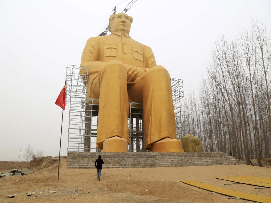 A man looks at the giant statue of Mao.