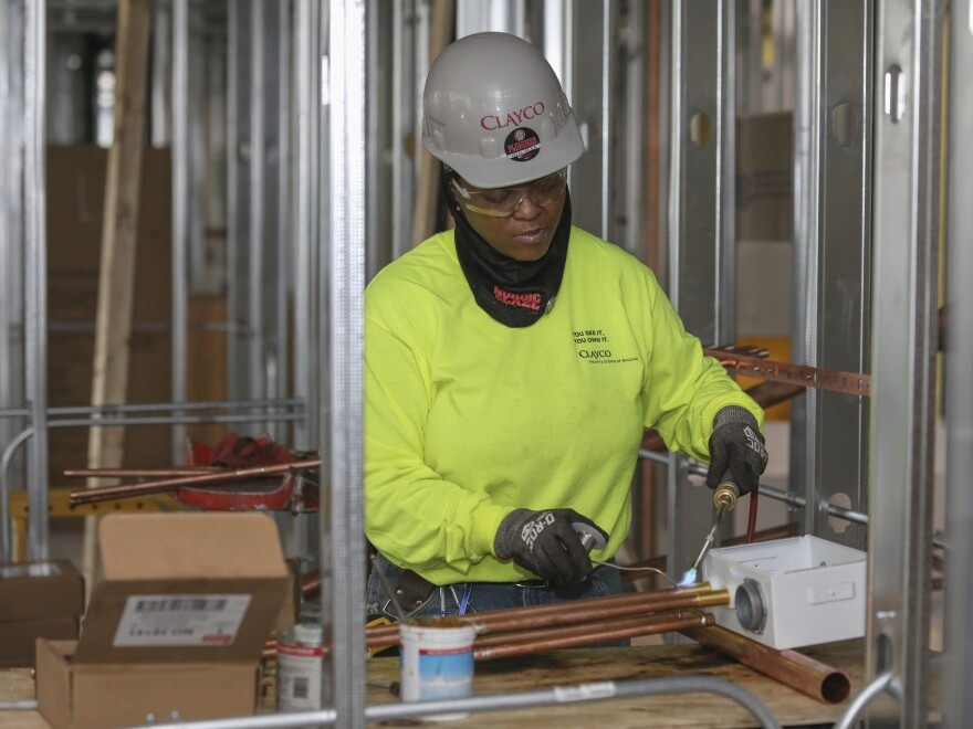 Plumber Zakiyyah Askia welds pipes at a high-rise residence under construction in Chicago on Jan. 24. U.S. employers added 196,000 jobs in March, a rebound from February's weak growth, the Labor Department said Friday.