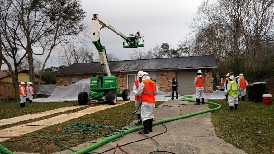 Dressed in protective gear, workers conduct cleanup operations at a home on Greenberry Drive in Cantonment near the IP plant.
