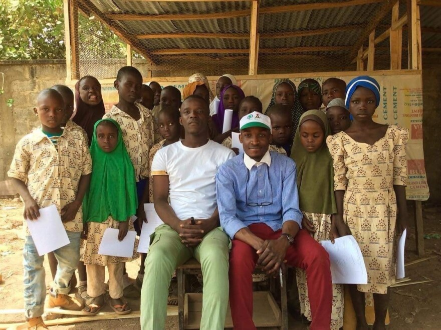 Aweofeso Adebola (in white shirt) and Ifeoluwa Ayomide (in cap) pose with some of their students. Zachariah Ibrahim, who dreams of being a pilot, stands behind the girl in the green hijab. Fatima Alidarunge, who wants to be a soldier to fight Boko Haram, is in the blue headgear.