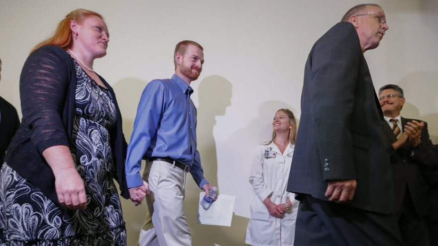 Ebola virus survivor Dr. Kent Brantly (center) and his wife, Amber (left), walk at a news conference at Emory University Hospital in Atlanta Thursday. Brantly and aid worker Nancy Writebol were discharged from the hospital less than a month after they contracted Ebola while treating patients in Liberia.