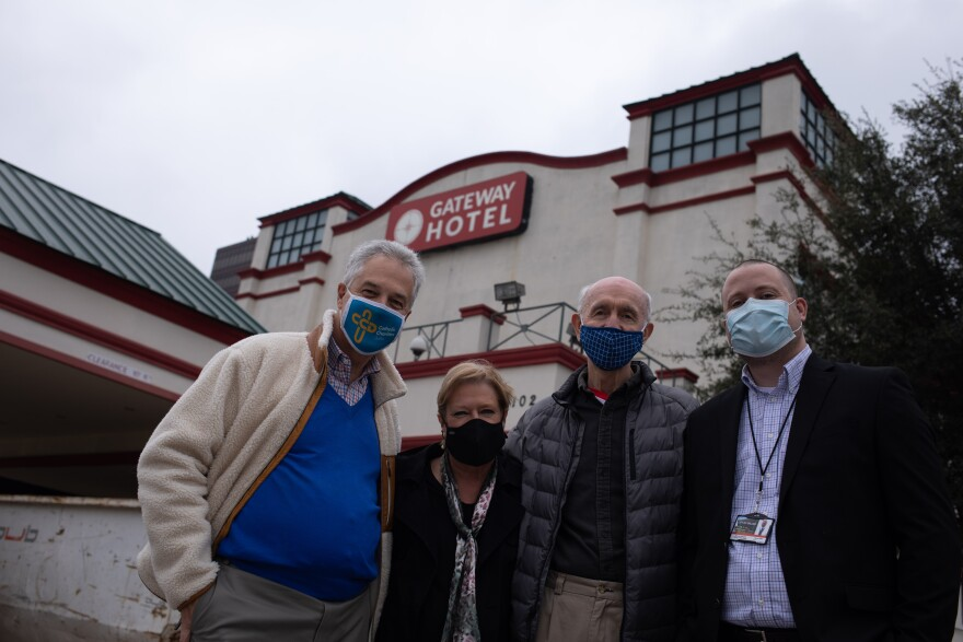 Four people wearing masks pose in front of the Gateway Hotel.