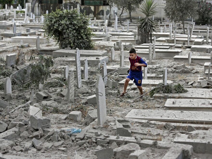 A Palestinian boy runs on the rubble of damaged graves at a cemetery hit by an Israeli strike in Gaza Cita, on Sunday.