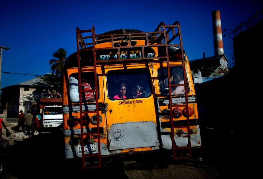 A woman watches from the back of a old school bus carrying passengers heading out of the capital and going north and to the city of Cap-Haïtien.