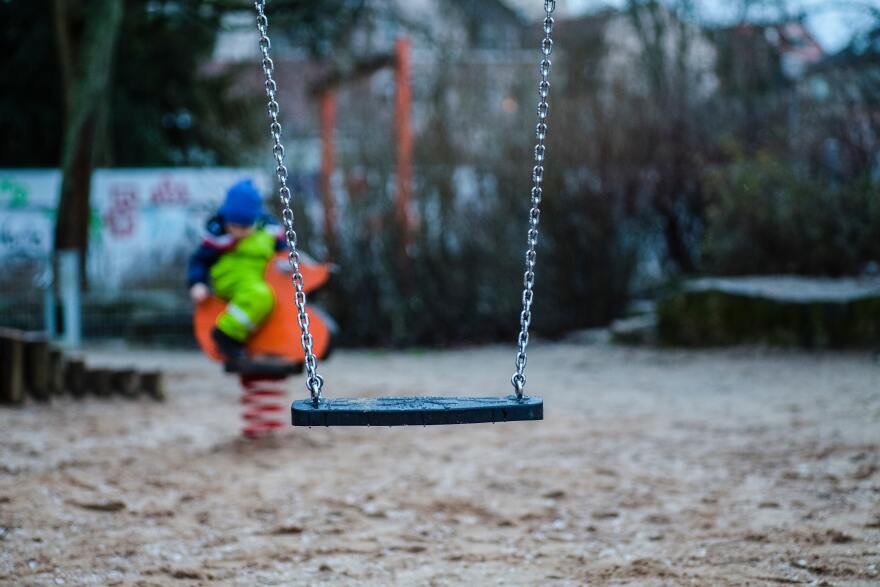 An empty swing on a playground. A child in bright green pants rides a springy orange duck in the background.